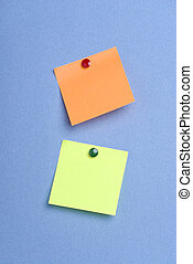 Green and orange pinned postits - Two post it notes with...