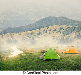 Green and orange tents on plain in mountains on foggy morning