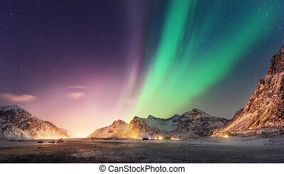 Green and purple aurora borealis over snowy mountains