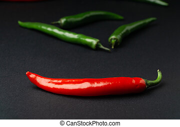 Green and red chili peppers on black background. Hot spicy food.