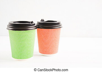 Green and red eco paper cups on white background with copy space