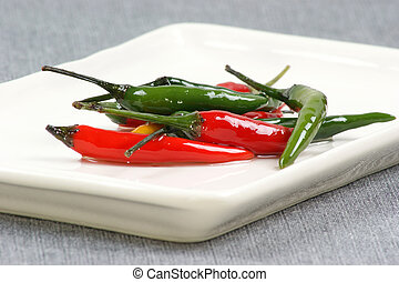 green and red hot pepper on a plate