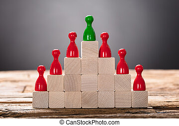 Green And Red Pawn Figurines Arranged On Wooden Blocks -...