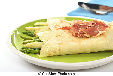 Green and white asparagus wrapped in crepes with ham as garnish on top (Selective Focus, Focus on the asparagus in the front and part of the ham)