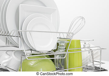 Green and white dishes drying on dish rack