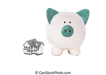 Green and white piggy bank standing beside miniature home