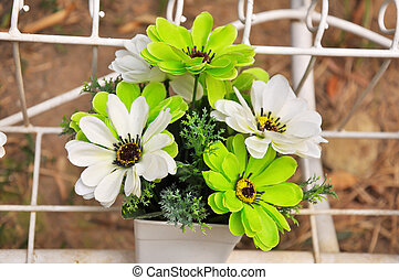 Green and white plastic flowers in a vase.