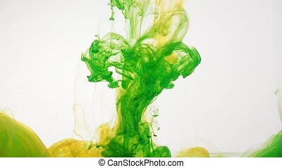 Green and yellow acrylic paint swirling in water on white background. Ink is moving mixed and intertwined creating abstract clouds. Traces of ink dissolving in water. 60fps, HD format