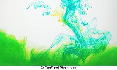 Green and yellow acrylic paint swirling in water on white background. Ink moving in water creating abstract clouds. Traces of colourful ink dissolving in water, ever changing shape. 60fps, HD format.