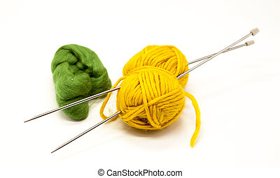 Green and yellow balls of yarn for knitting with spokes on a white background.