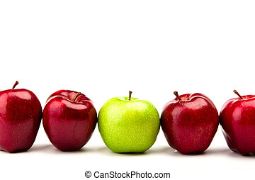 Green apple among red apples isolated on a white