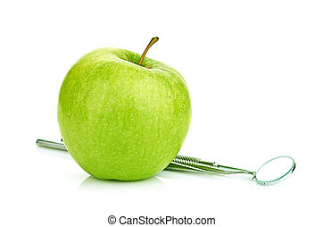 Green apple and dental tools isolated on white