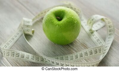 Green apple and tape measure - Closeup green apple with...