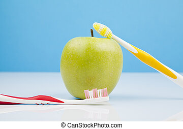 green apple and toothbrushes