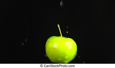 green apple, close - up. Drops of water fall on a rotating apple on a black background. super slow-motion.