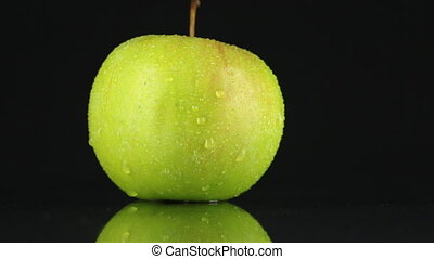 Green apple  in drops of dew rotates on its axis. HD