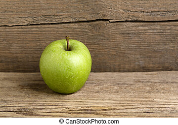 Green apple on a wooden background