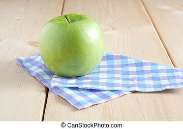 Green apple on a wooden table