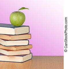 Green apple on books on desk