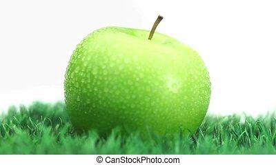 Green apple on grass rotating