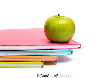 Green apple on notebooks