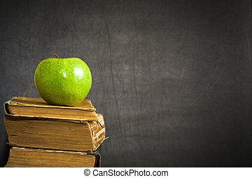 Green apple on old book against blackboard
