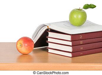 Green apple on open book