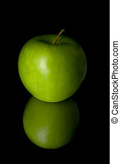 Green apple on the black background