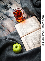 Green apple, tea, book and blanket on a wooden background