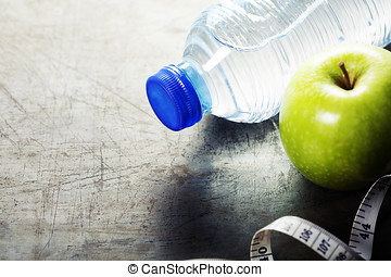 Green apple, water and measuring tape. Health and diet...