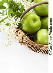 Green apple with flowers in a basket on a white background
