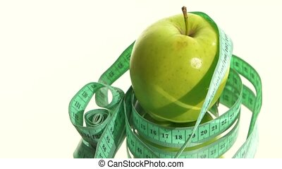 Green apple with measuring tape on white, rotation, reflection