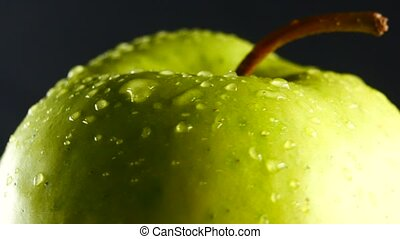 green apple with water drops rotates on black background