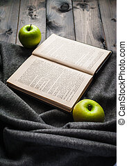 Green apples, book and blanket on a wooden background