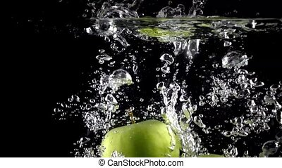 Green apples fall down in water against black background, super slow motion