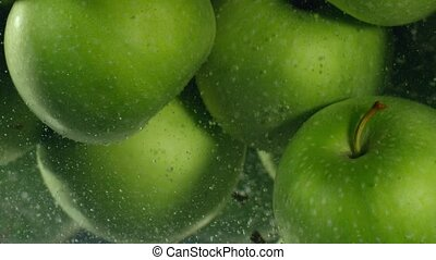 Green apples fall down in water against black background,...