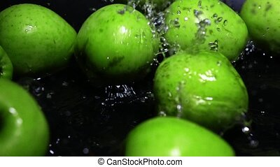 Green apples falling in water super slow motion video
