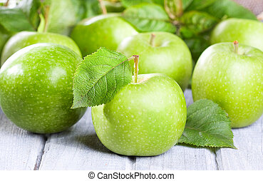 green apples - fresh apples with leaves on wooden table