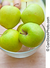 Green apples in a glass bowl