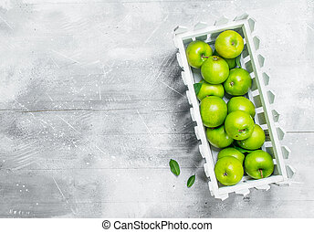 Green apples in a plastic box.