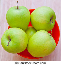 Green apples in a red bowl