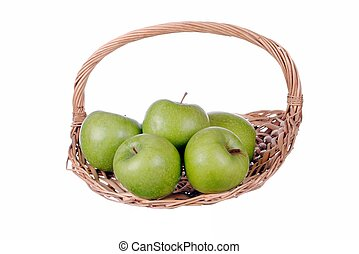 green apples in a straw basket, isolated on white