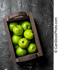 Green apples in a wooden box.