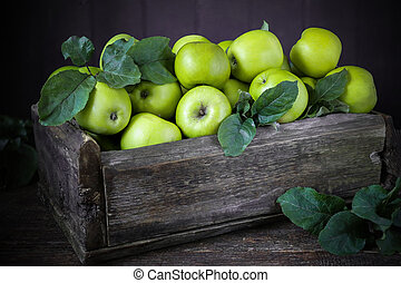 Green apples in a wooden box on old boards