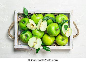 Green apples in a wooden tray.