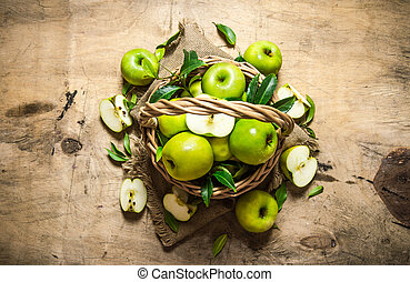 Green apples in an old basket. On wooden table. Top view