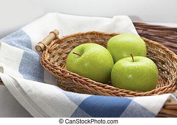 Green apples in the brown wicker basket