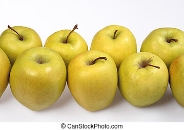 Green apples in two rows on a white background close-up, side view.