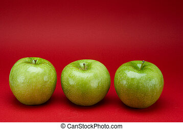 Green apples on a red background