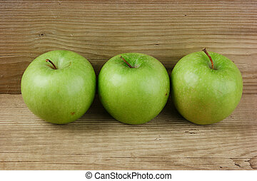 green apples on a wooden background